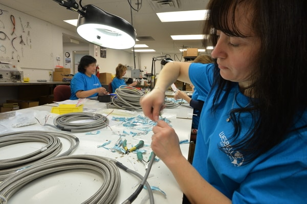 Photo of employee preparing a braided stainless steel shielded PVC multiconductor cable order.